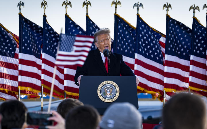 President Donald Trump speaks to supporters at Joint Base Andrews before boarding Air Force One for his last time as President.